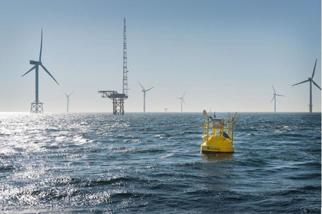 A floating LiDAR in front of a fixed met mast in an offshore wind farm. Photo: Frauenhofer IWES